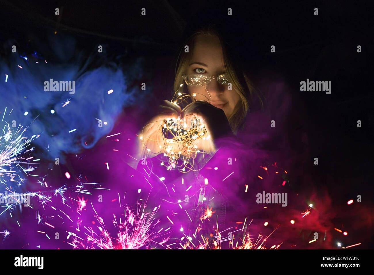 Portrait de femme en forme de coeur avec chaîne illuminé par des feux la nuit des étincelles colorées Banque D'Images