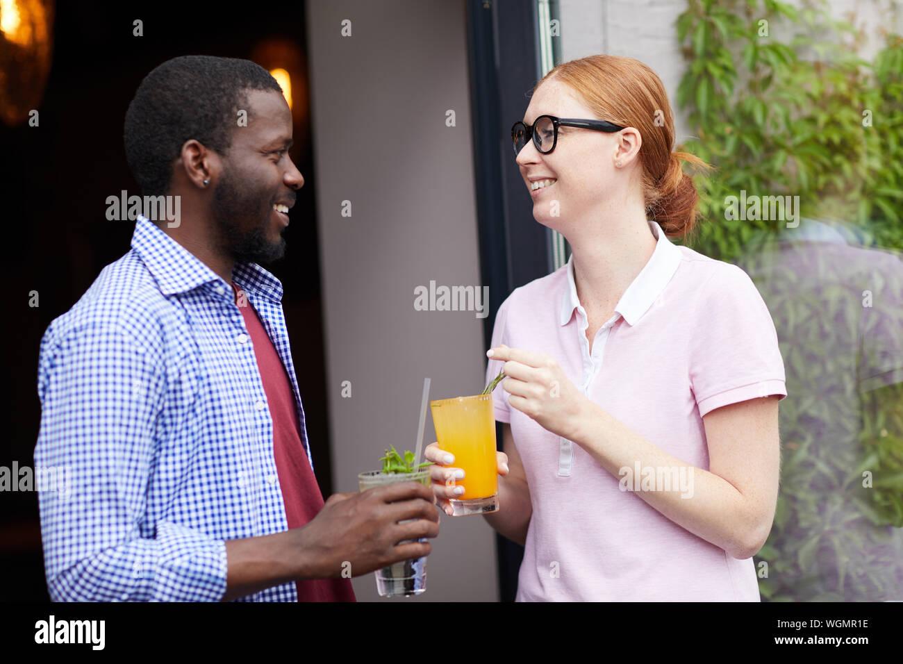 Waist up portrait of smiling young woman talking to African man à l'extérieur, à la fois froid maintenant des boissons rafraîchissantes, copy space Banque D'Images