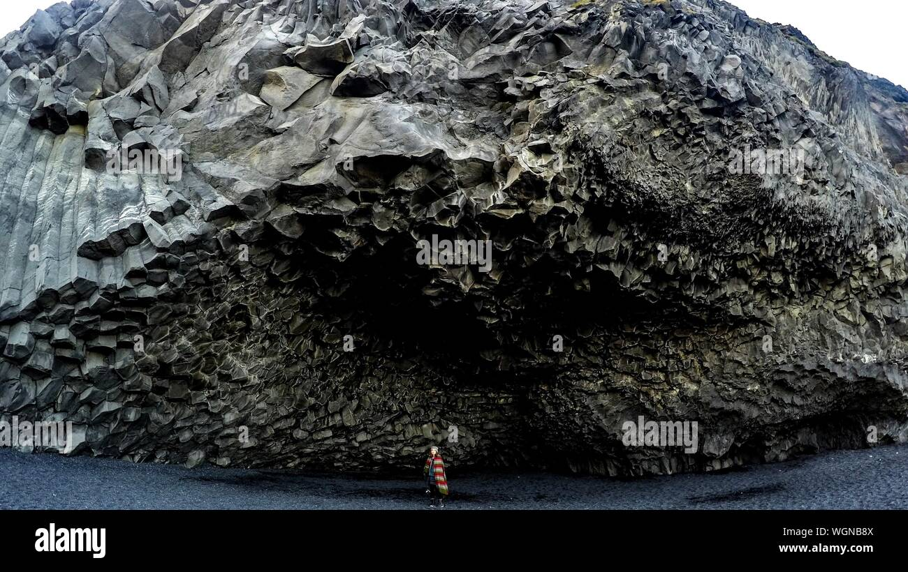 Woman Standing Under Rock Formation Banque D'Images