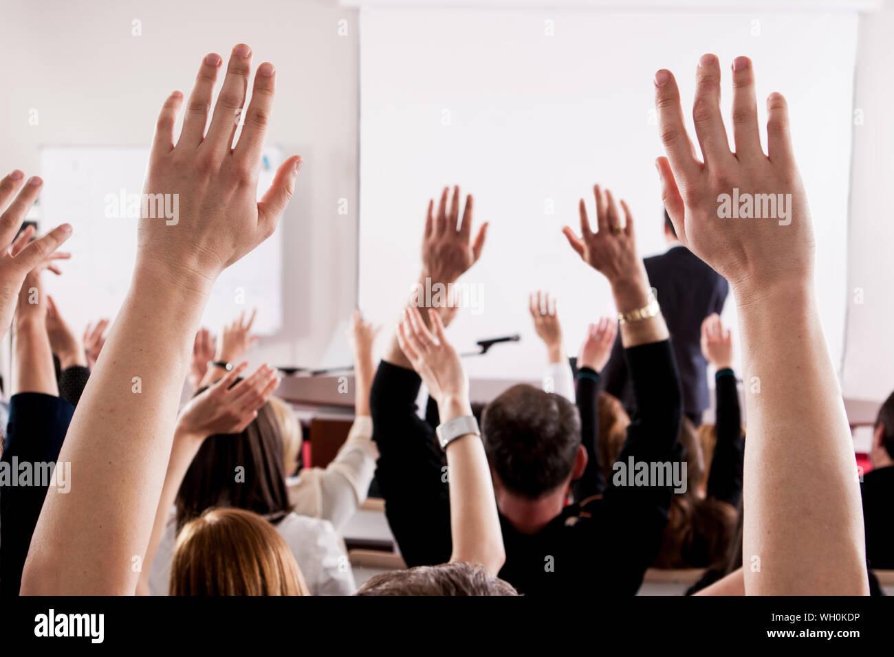 People With Arms raised in Lecture Hall au cours de séminaire Banque D'Images