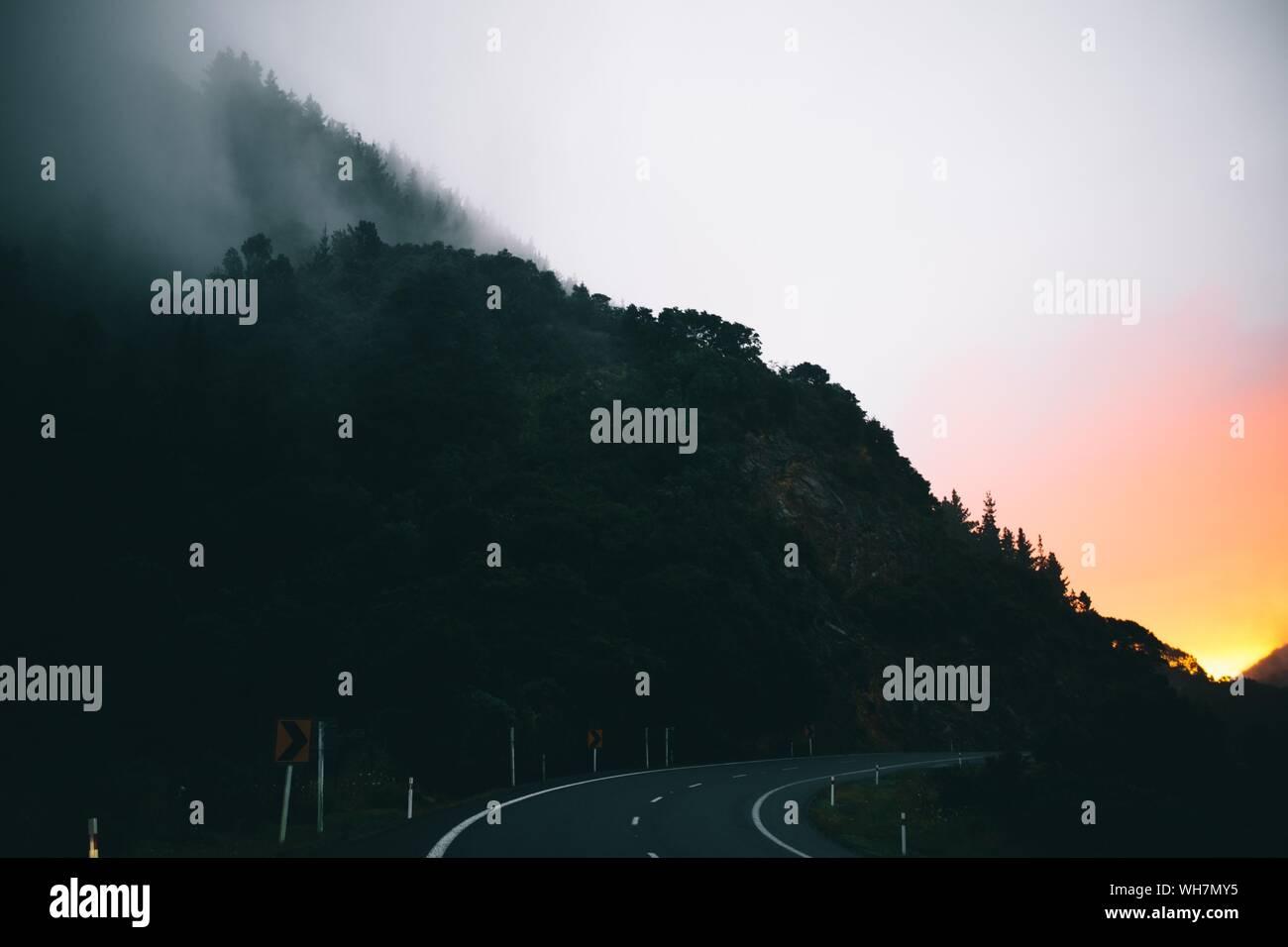 Par la route de montagne arbre vide Against Sky Banque D'Images