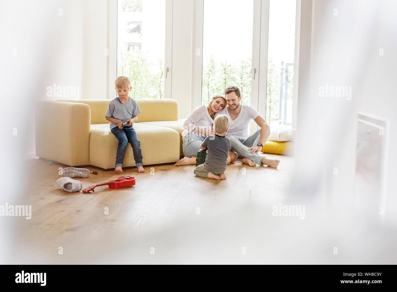 Famille heureuse avec deux fils jouant dans la salle de séjour de leur nouvelle maison Banque D'Images