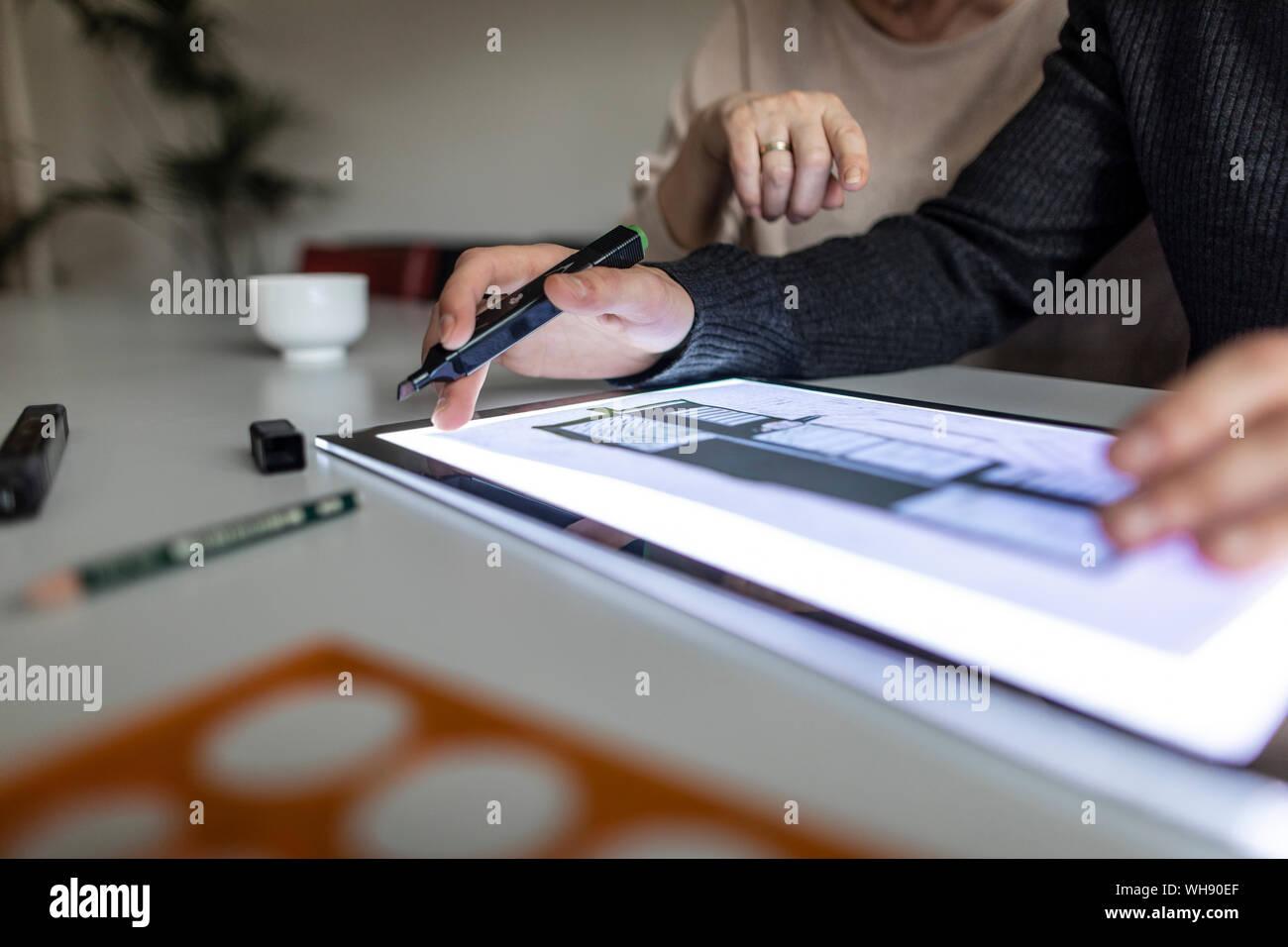 Close-up de l'homme à l'aide de tablette avec plan d'architecture Banque D'Images