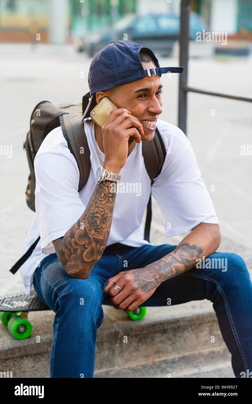 Portrait de jeune homme tatoué sur le téléphone assis sur son skateboard en plein air Banque D'Images