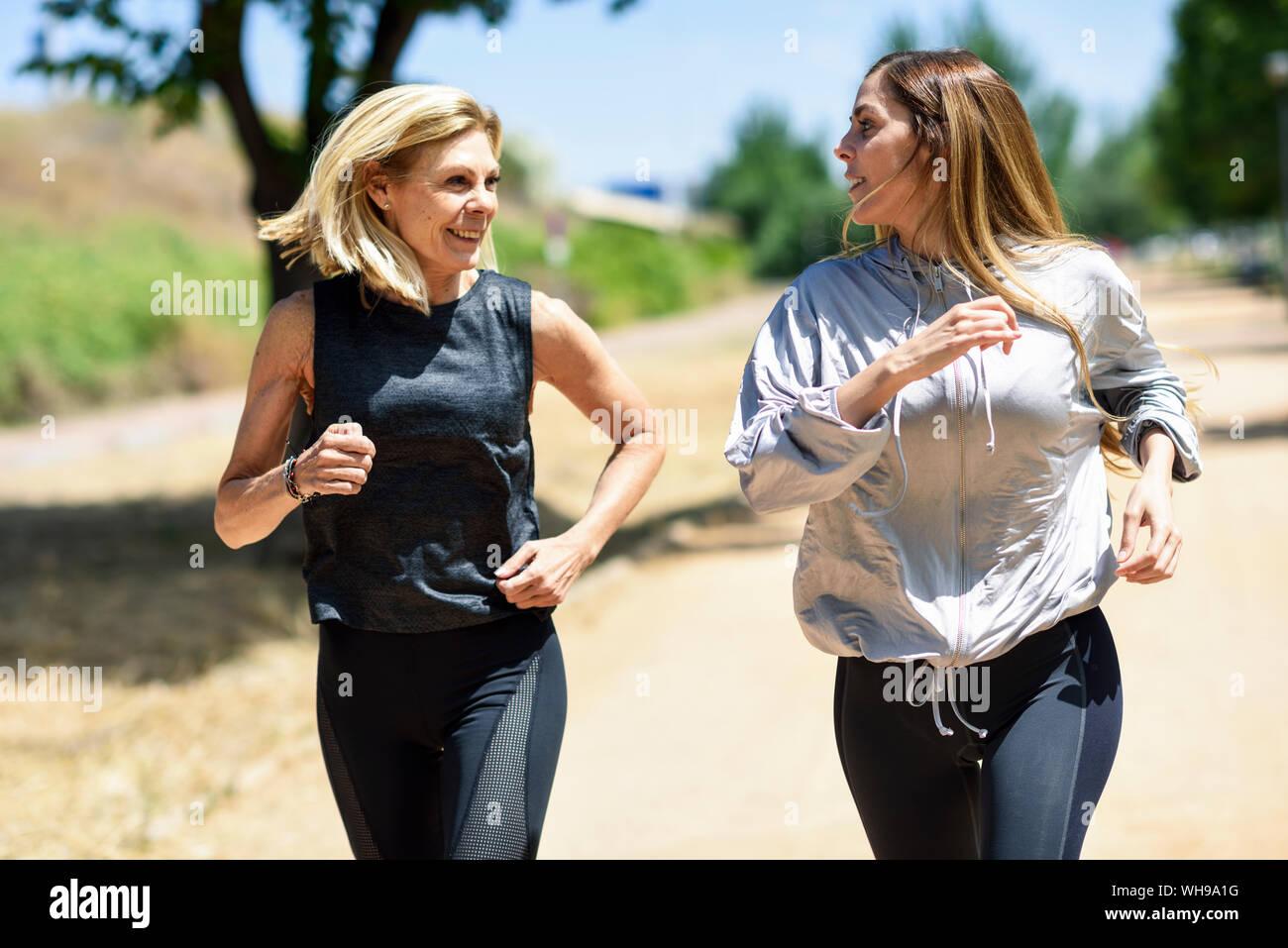 Young woman running avec sa fille dans un parc Banque D'Images