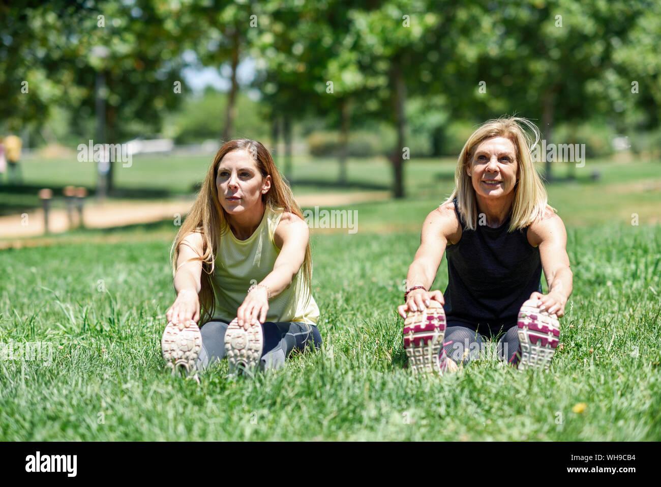 Femme mature et sa fille s'étend les jambes sur un pré dans un parc Banque D'Images