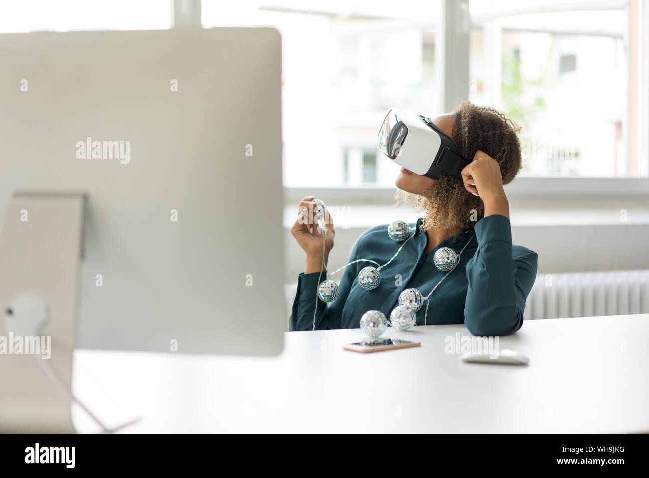 Jeune femme assise au bureau avec lumières à l'aide de lunettes de réalité virtuelle Banque D'Images