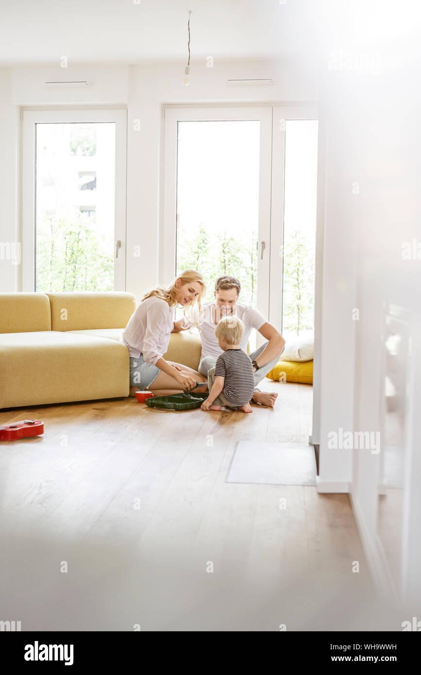 Famille heureuse avec un fils jouer dans la salle de séjour de leur nouvelle maison Banque D'Images