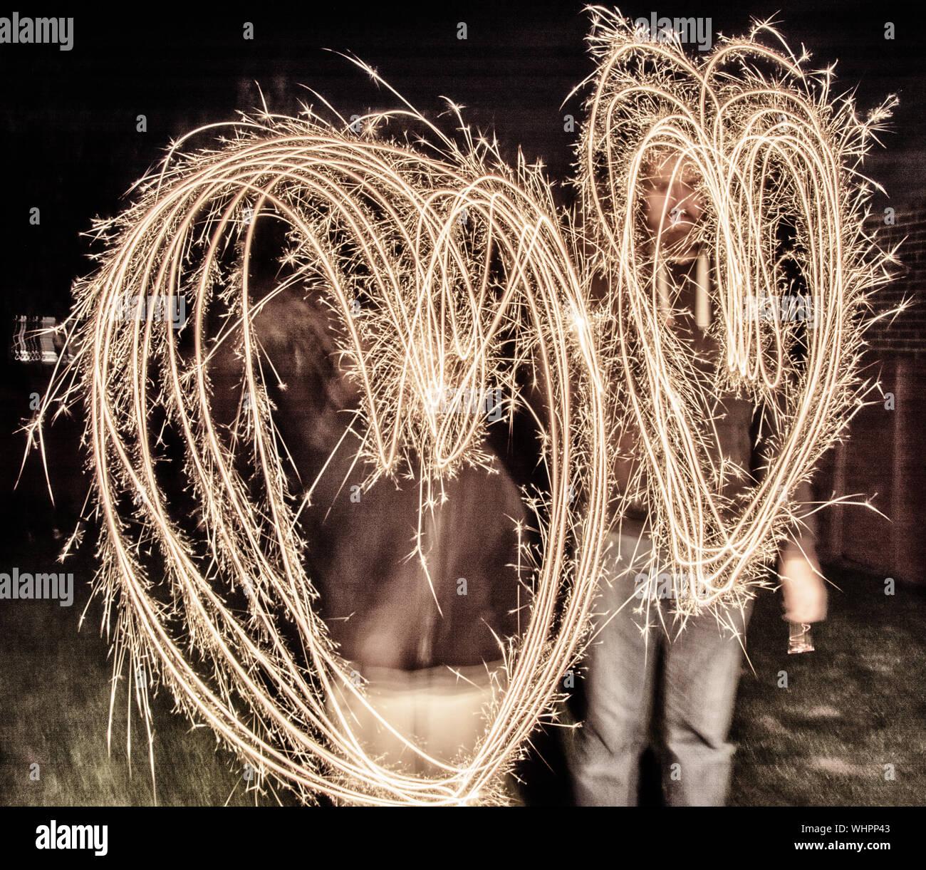 Hommes qui forme de coeur avec cierges dans la nuit Banque D'Images