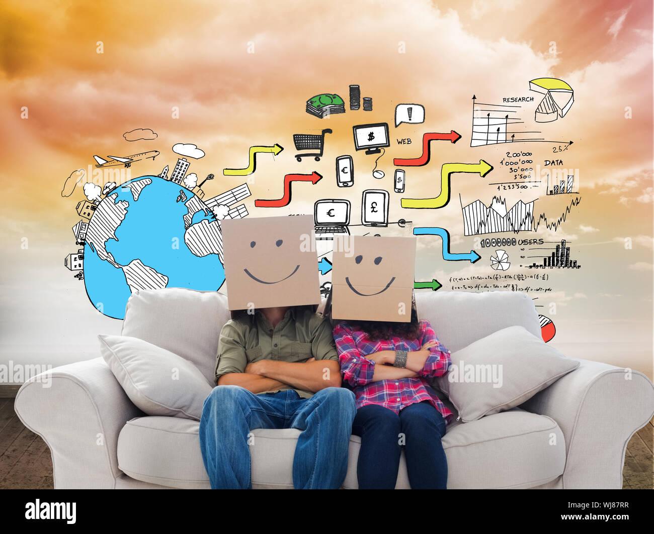 Image composite de silly employés avec bras croisés portant sur leurs têtes des boîtes avec des smileys sur un canapé Banque D'Images