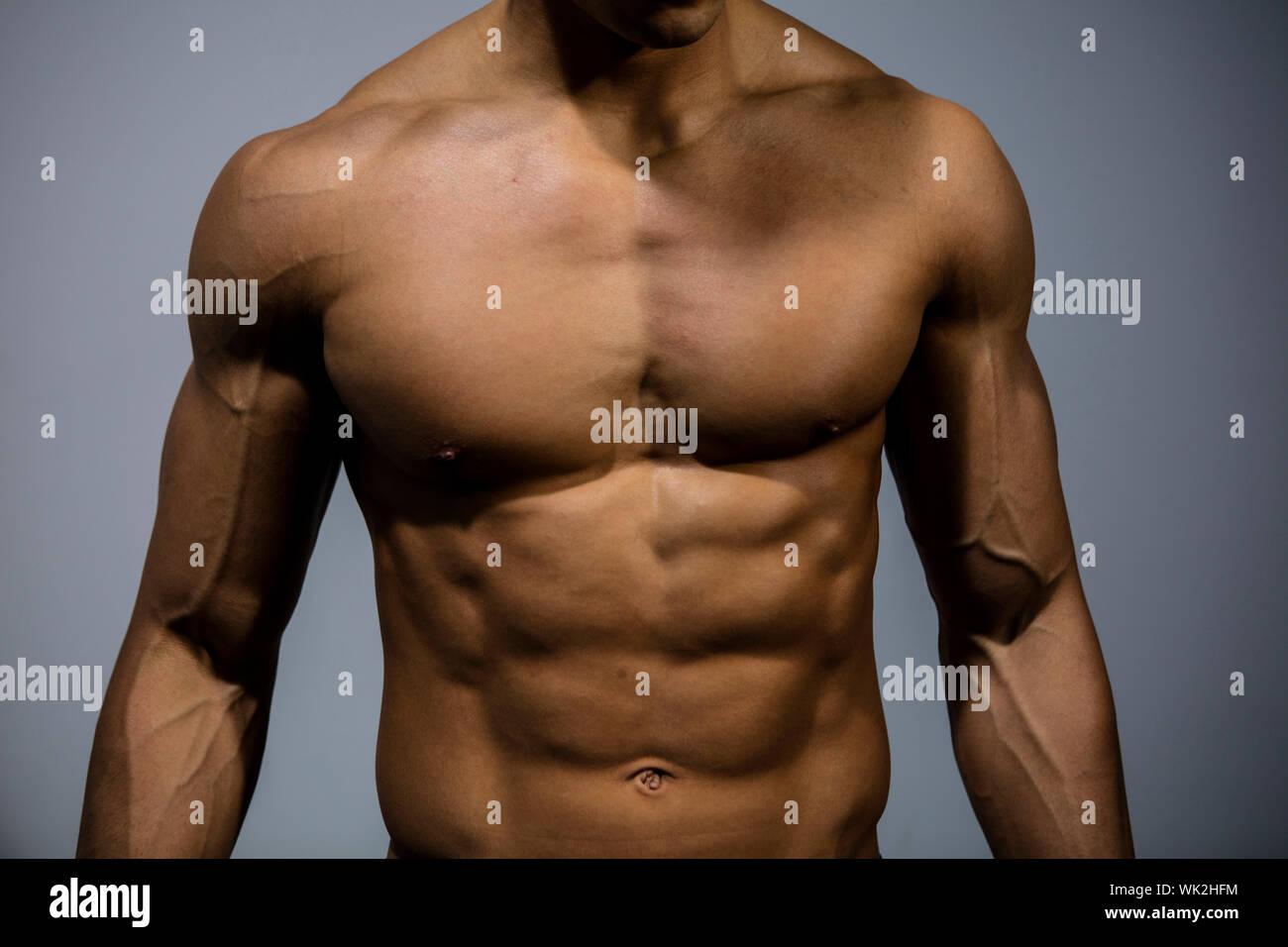 Au milieu du torse nu musclé Homme debout contre le mur Banque D'Images