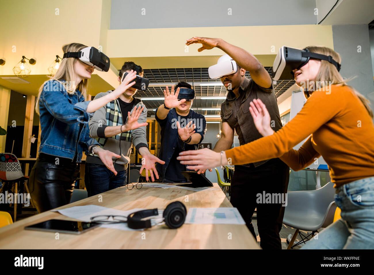Les jeunes gens d'affaires multiraciale portant des lunettes de réalité virtuelle avec le toucher d'air au cours de la Conférence Réunion VR au bureau. Les hommes et femmes d'affaires Banque D'Images