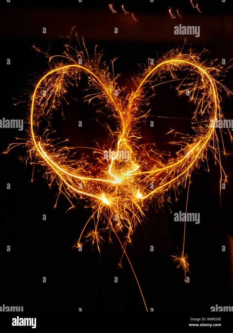 Peinture de lumière en forme de coeur de Sparkler la nuit Banque D'Images