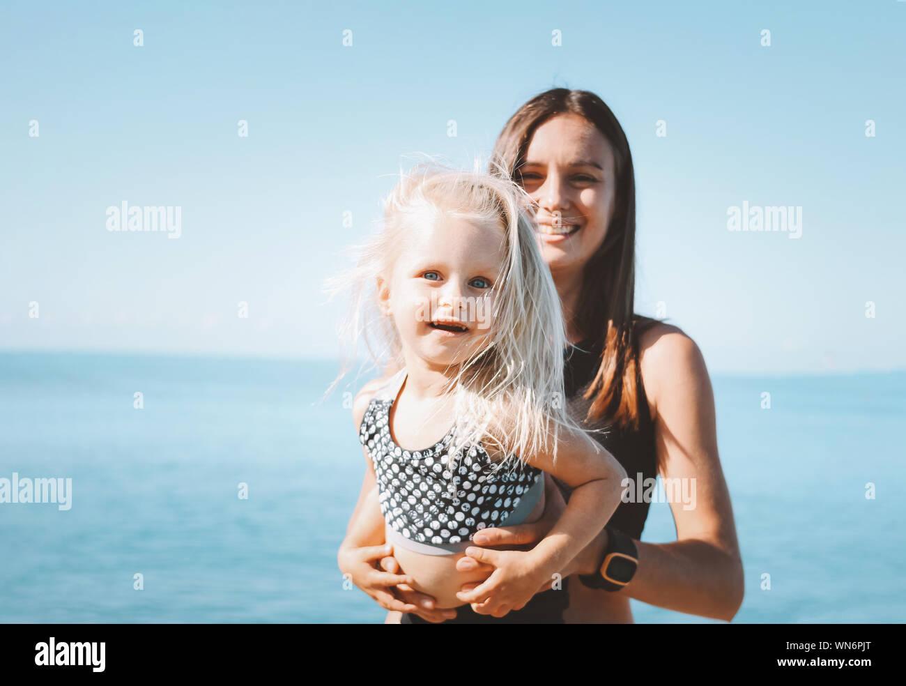 Les jeunes fit woman maman avec peu cute girl l'exercice sur la plage ensemble, le mode de vie sain Banque D'Images