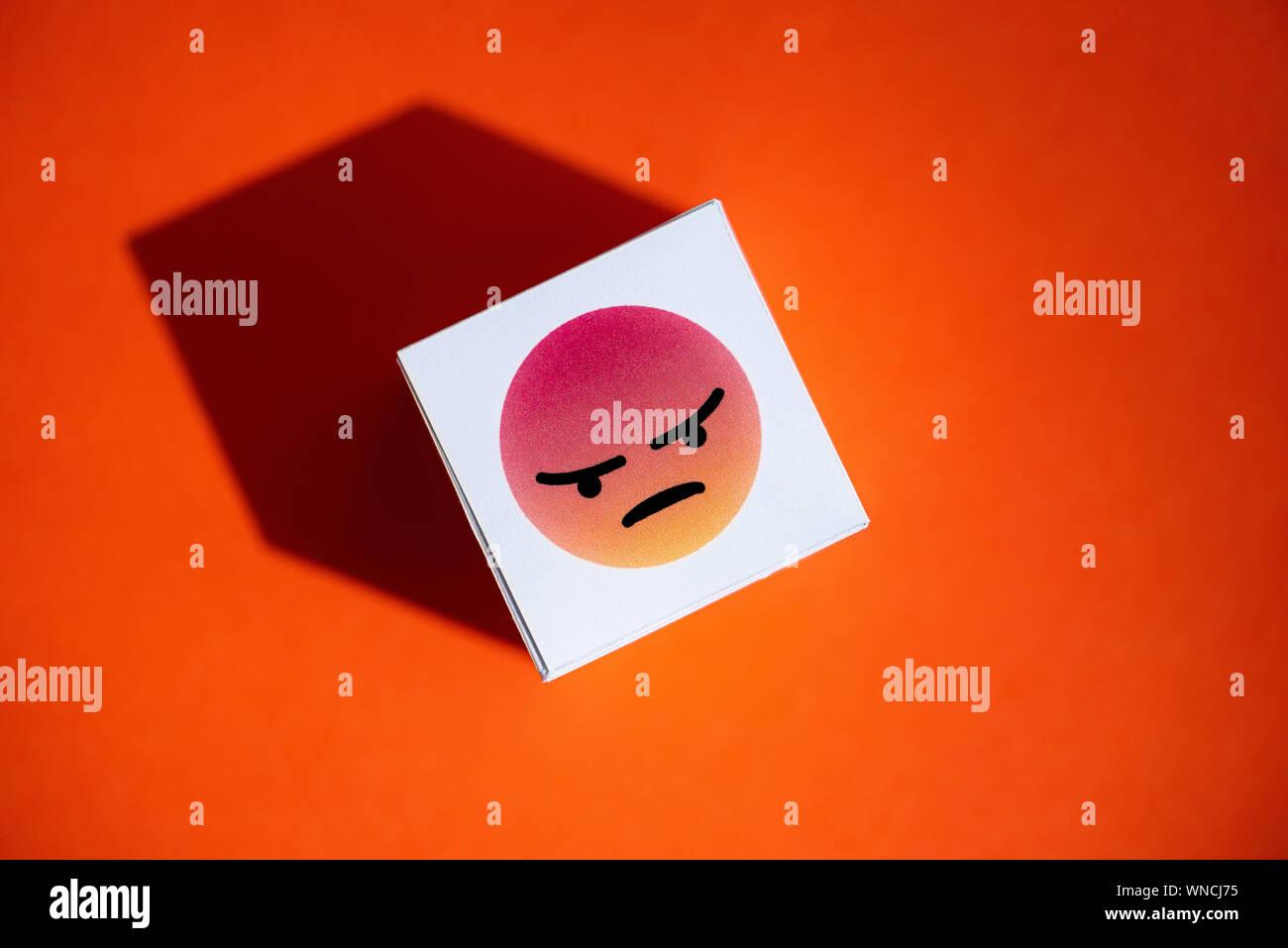 La colère d'un symbole à partir d'Emoji Facebook Messenger imprimé sur papier, qu'un cube placé sur un fond orange. Banque D'Images