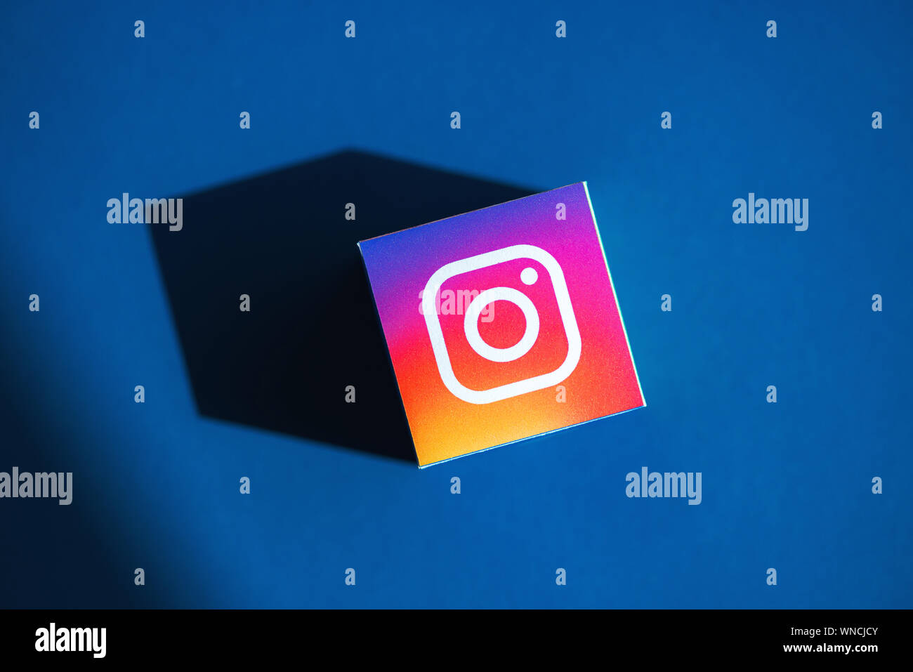 Un coup de feu au-dessus du cube papier imprimé avec le logo de l'application Instagram, qui a placé sur un fond bleu. Banque D'Images