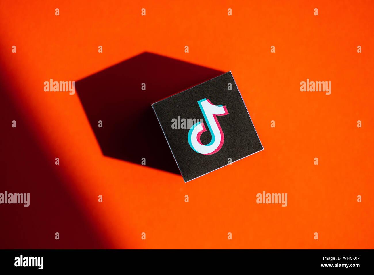 Un coup de feu au-dessus du cube papier imprimé avec le logo de l'application, qui a placé TikTok sur fond orange. Banque D'Images