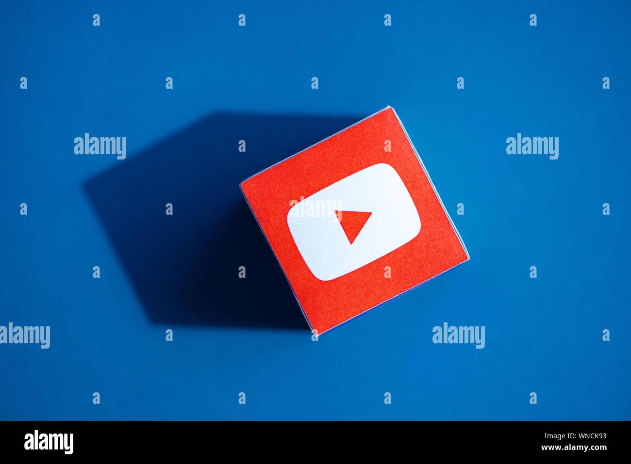 Un coup de feu au-dessus du cube papier imprimé avec le logo de l'application YouTube, qui a placé sur un fond bleu. Banque D'Images