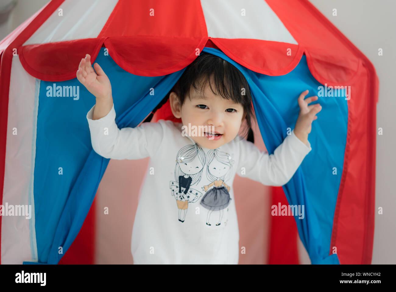 Asian cute girl standing in robe blanche en tente lodge et sourire dans la salle de séjour à la maison. Banque D'Images