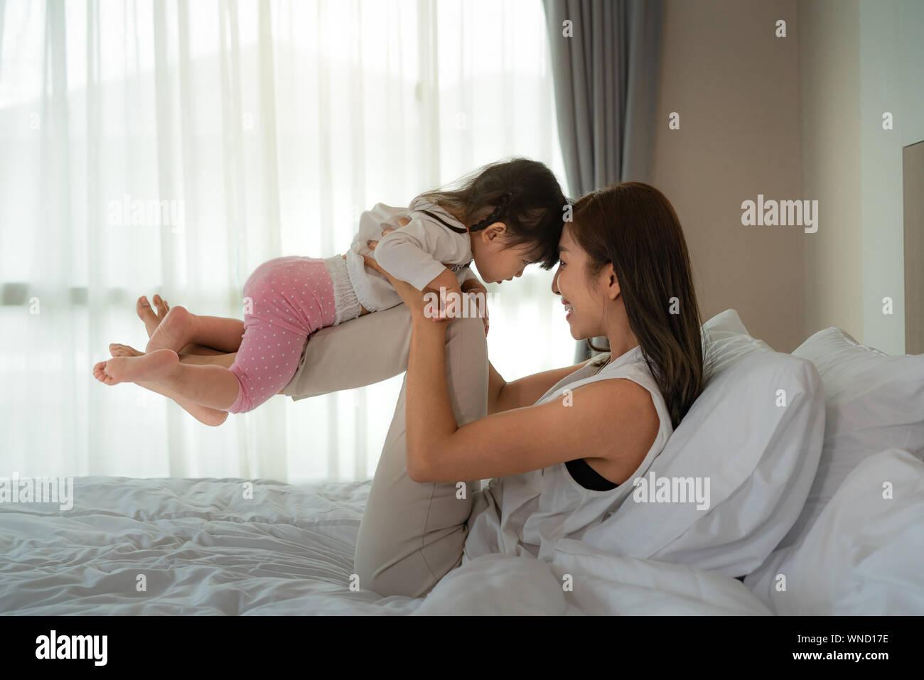 Portrait of happy laughing baby hugging avec cheerful young smiling mother, scène de pur amour et bonheur. Famille, de la maternité et de style de concept Banque D'Images