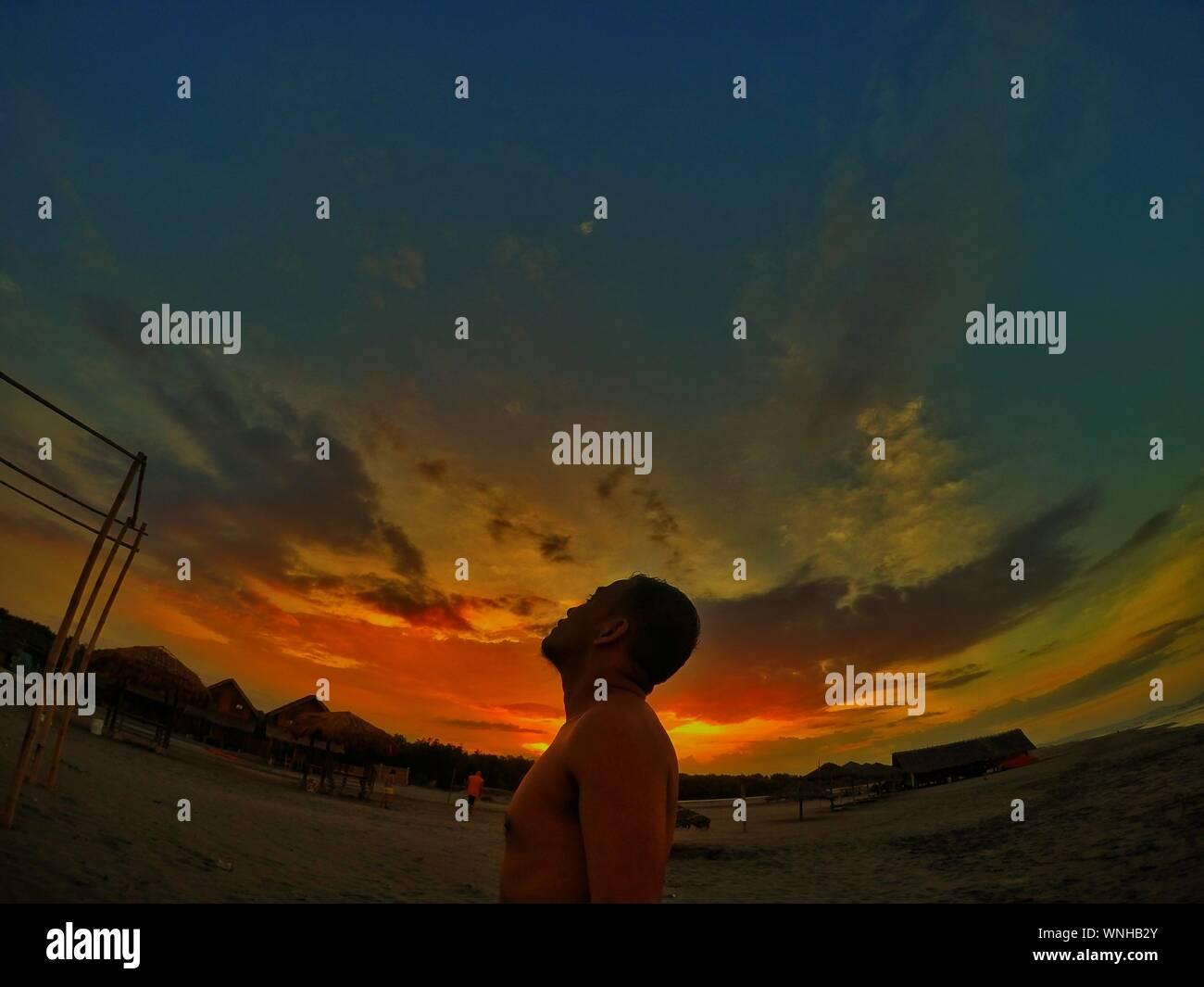 Shirtless Man Standing On Field Against Cloudy Sky pendant le coucher du soleil Banque D'Images
