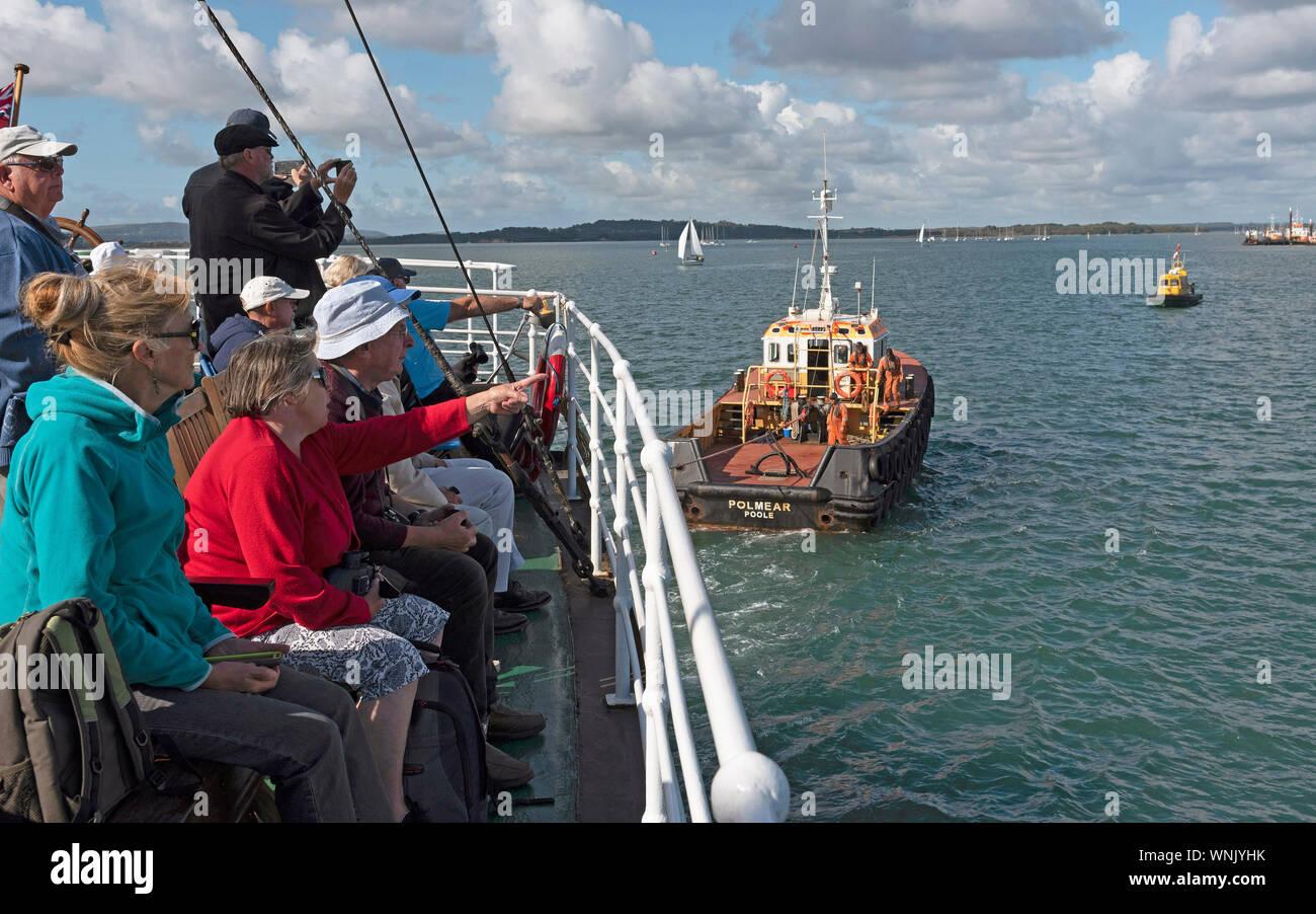 Le port de Poole, Dorset, England, UK. Septembre 2019. Remorqueur assiting SS Shieldhall du poste à quai vu par les passagers assis à l'arrière Banque D'Images