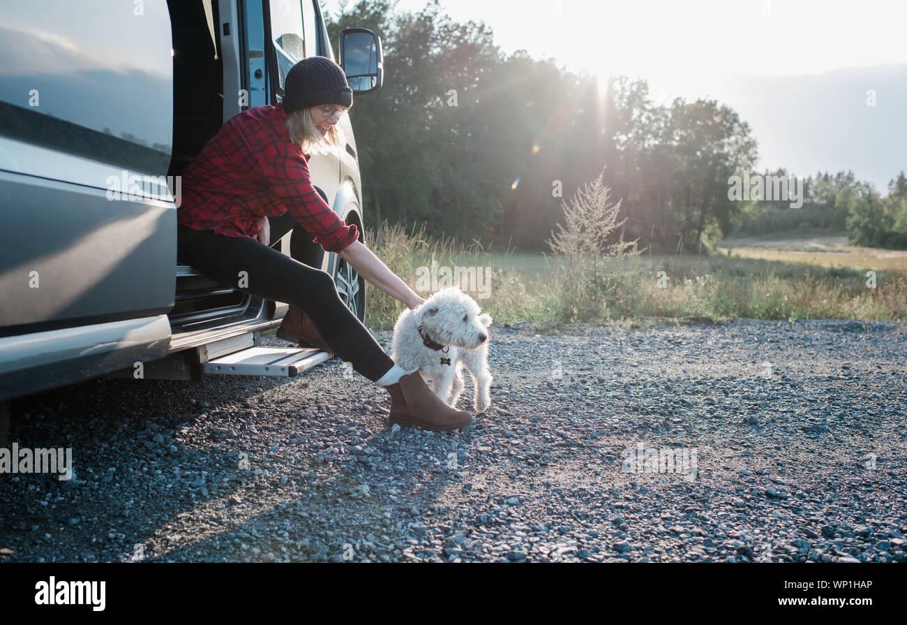 Femme assise sur un camping-car de caresser son chien tout en camping Banque D'Images