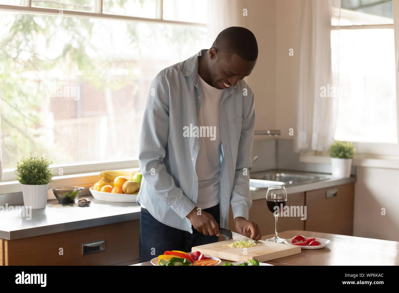 Smiling African American man preparing food in kitchen Banque D'Images