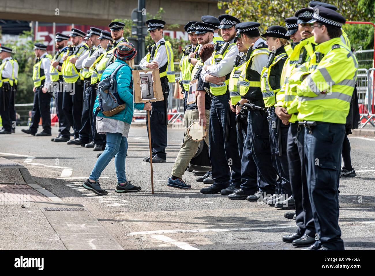 Petite femme manifestant avec cordon de police au sein de la Défense et Sécurité internationale de l'équipement Foire aux armements dees trade show, ExCel, Londres, UK Banque D'Images