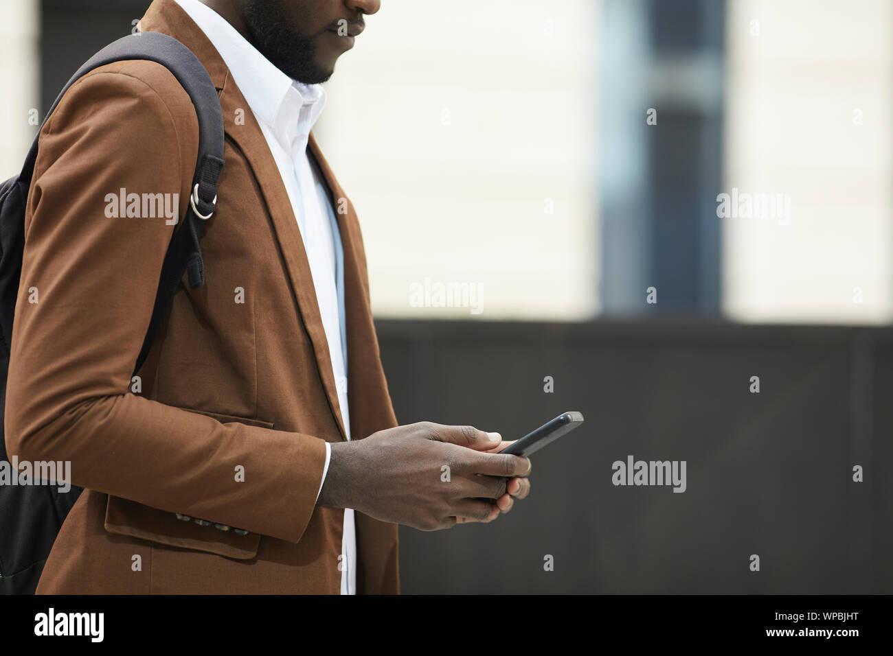 Mid section Vue de côté de l'homme afro-américain holding smartphone et la saisie des messages texte en milieu urbain, copy space Banque D'Images