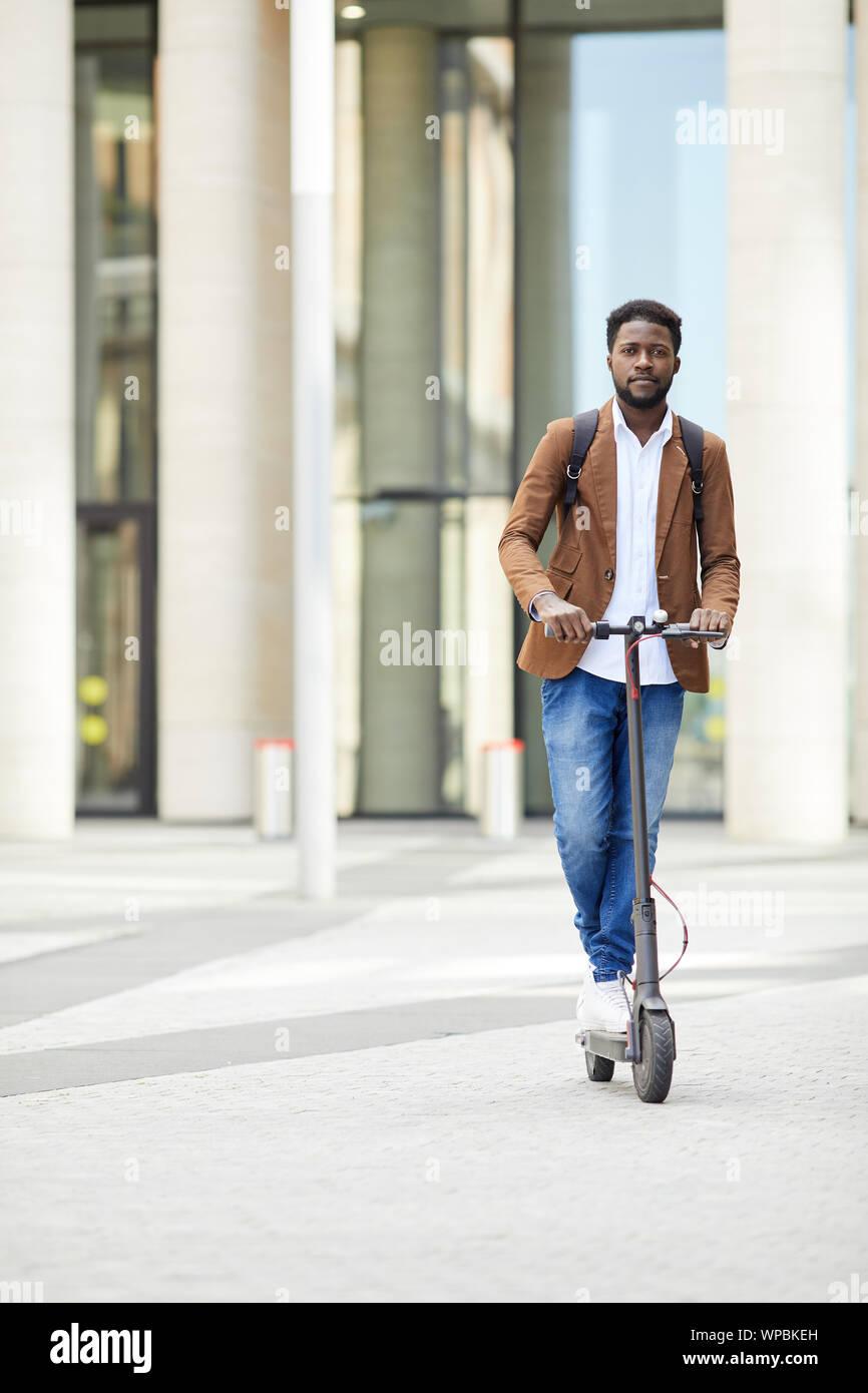Portrait de l'homme afro-américain contemporain riding scooter électrique et looking at camera lors des trajets dans les rues de la ville, copy space Banque D'Images