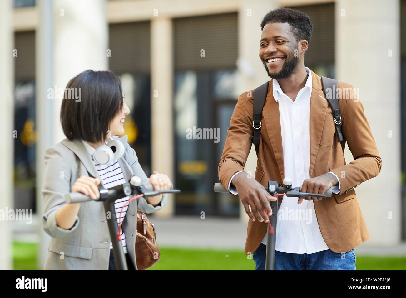 Groupe multiethnique de cheerful young people riding scooter électrique en ville rue et souriant heureusement regarder, copy space Banque D'Images