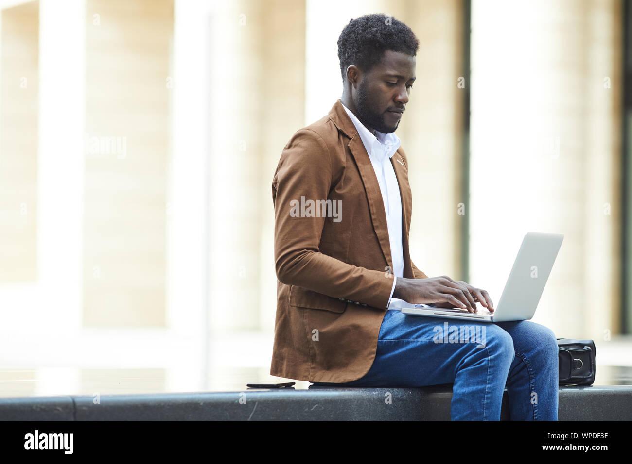 Side view portrait of young man afro-américaines à l'extérieur tout en travaillant sur un projet d'affaires en milieu urbain, copy space Banque D'Images