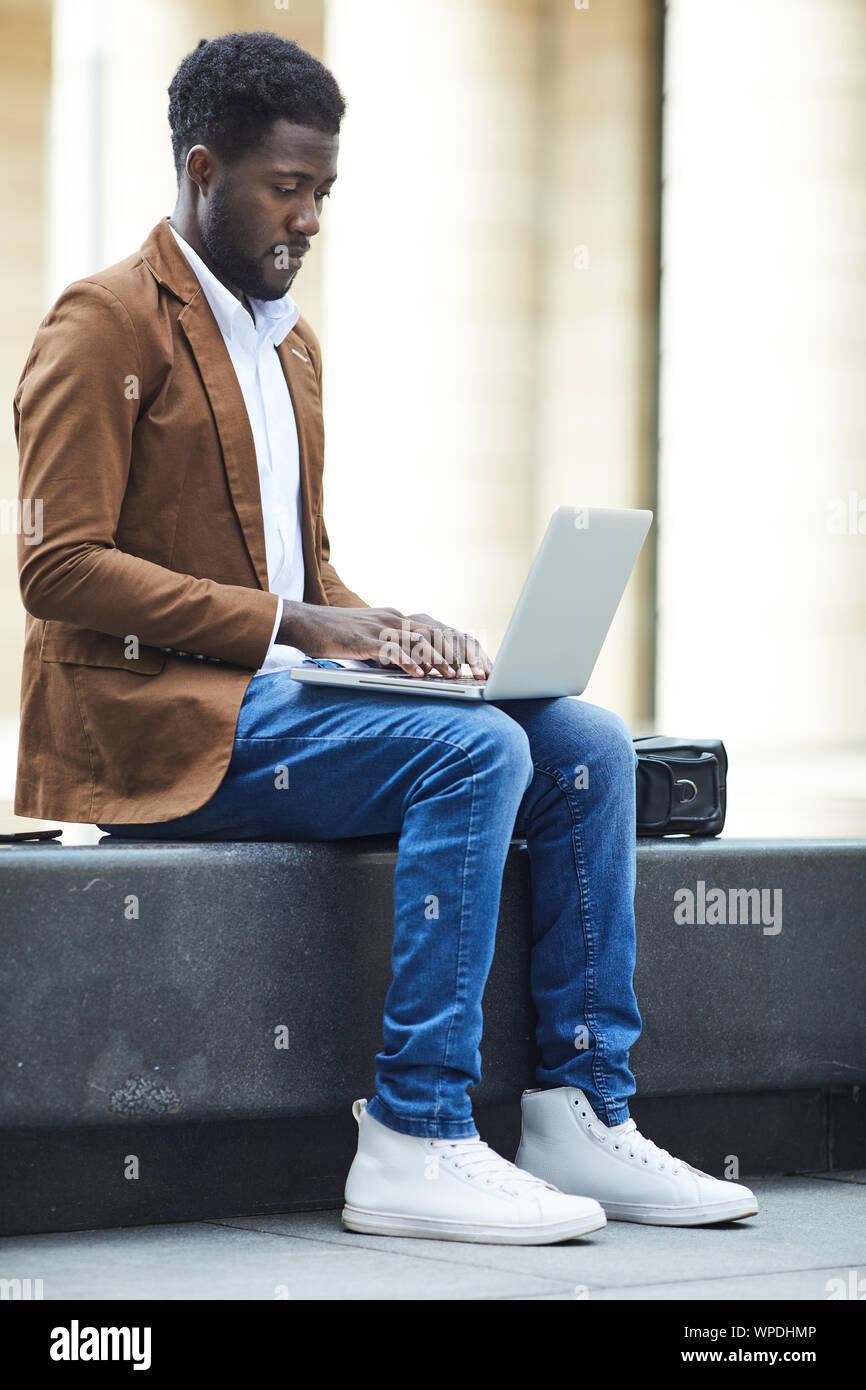 Vue latérale sur toute la longueur de jeunes afro-américain à l'aide d'ordinateur portable à l'extérieur tout en travaillant sur des missions en milieu urbain, copy space Banque D'Images