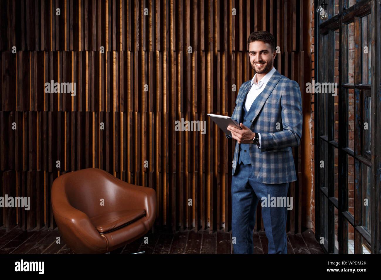 Jeune homme avec une barbe dans un luxueux costume bleu vérifié. L'homme travaille sur une tablette dans un loft bureau. Banque D'Images