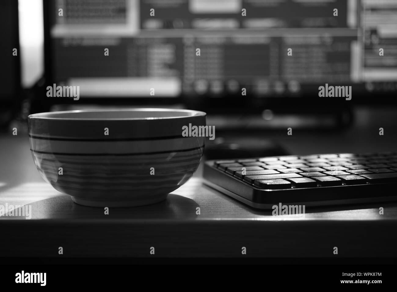 Espace de travail indépendant, tasse de thé, de clavier et le moniteur, de l'environnement de travail, photo en noir et blanc. Banque D'Images