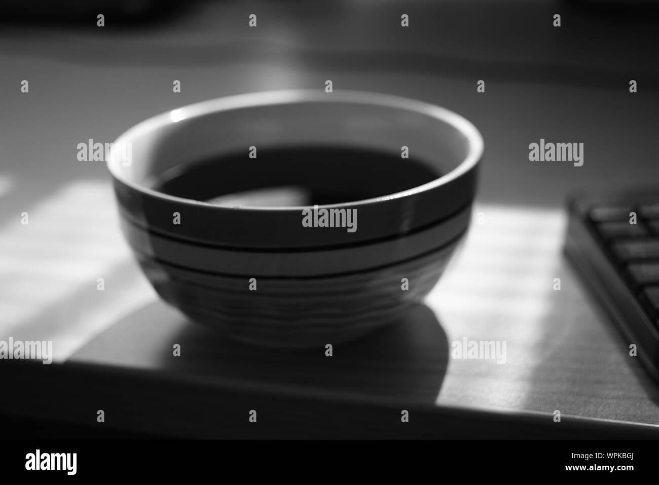 Grand bol tasse de thé et d'une partie de clavier, de l'environnement de travail, selective focus, photo en noir et blanc. Banque D'Images