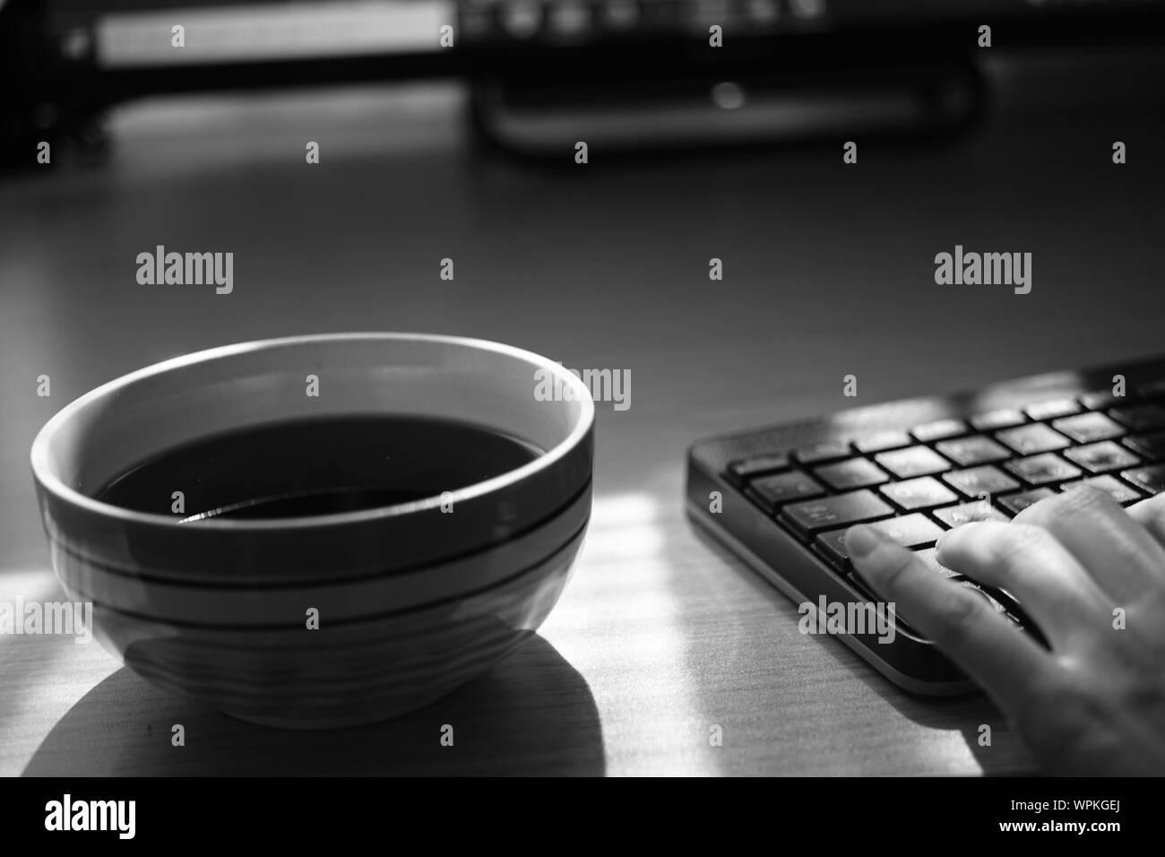 Travail indépendant avec tasse de thé et le clavier sur la table, de l'environnement de travail, selective focus, photo en noir et blanc. Banque D'Images