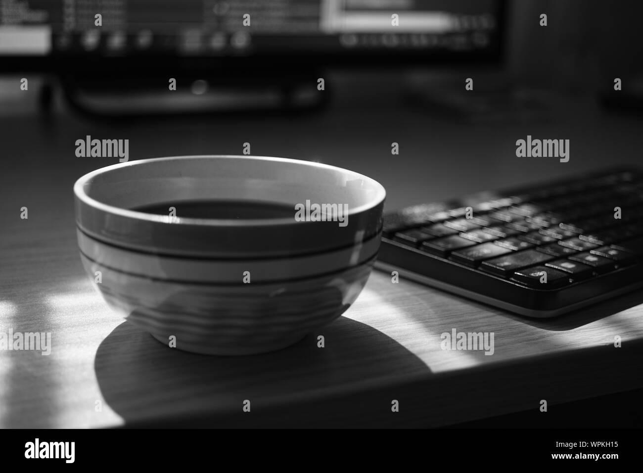 Espace de travail indépendant, tasse de thé, de clavier et le moniteur, de l'environnement de travail, selective focus, photo nb. Banque D'Images