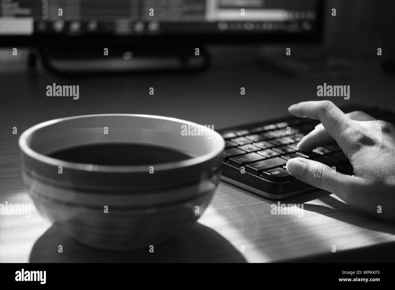 Lieu de travail dans le bureau avec une tasse de thé et un clavier sur la table, de l'environnement de travail, selective focus, photo nb Banque D'Images
