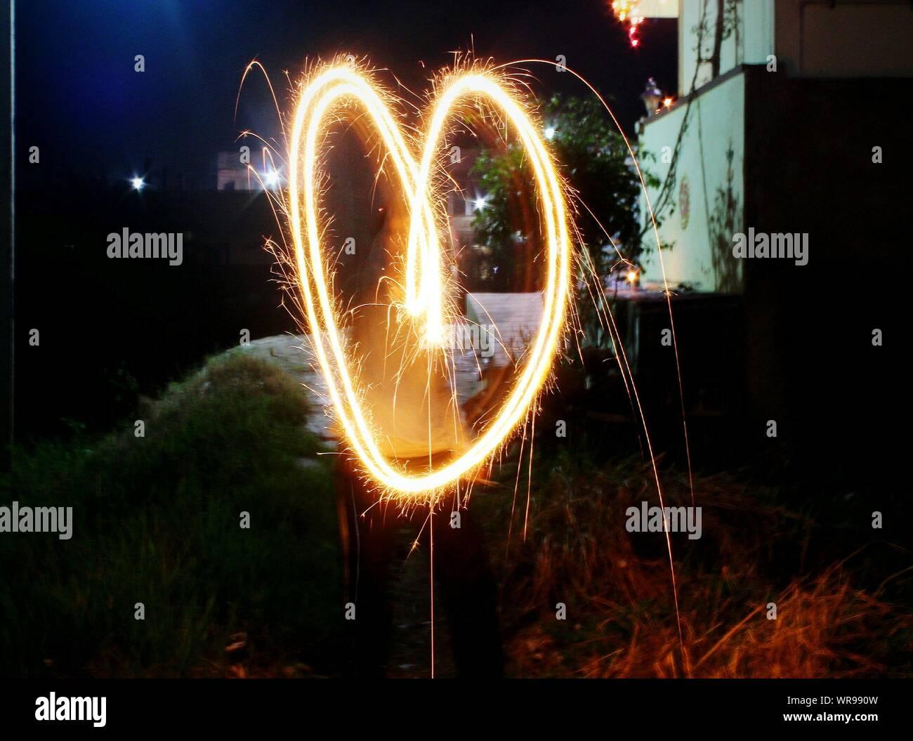 Forme de coeur formé de Burning Sparkler la nuit Banque D'Images
