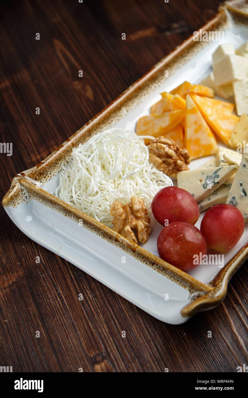 Belle table assiette de fromage sur une plaque blanche sur fond sombre.Close up, vue du dessus. Style alimentaire. Restaurant menu Banque D'Images
