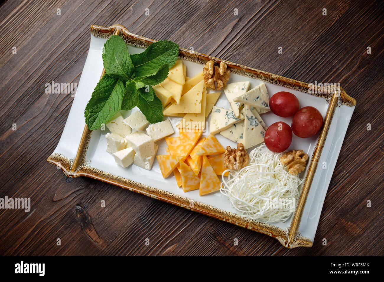 Belle table assiette de fromage sur une plaque blanche sur un fond sombre. Style alimentaire. Restaurant menu Banque D'Images