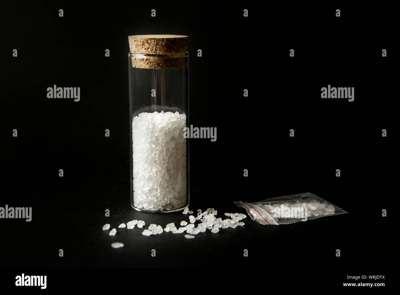 """Image conceptuelle de """"sels de bain"""" drogue stupéfiants concept. La poudre de cristal blanc sur fond noir( mis en place), ressemblent à des bains de sels de bain. Banque D'Images"""