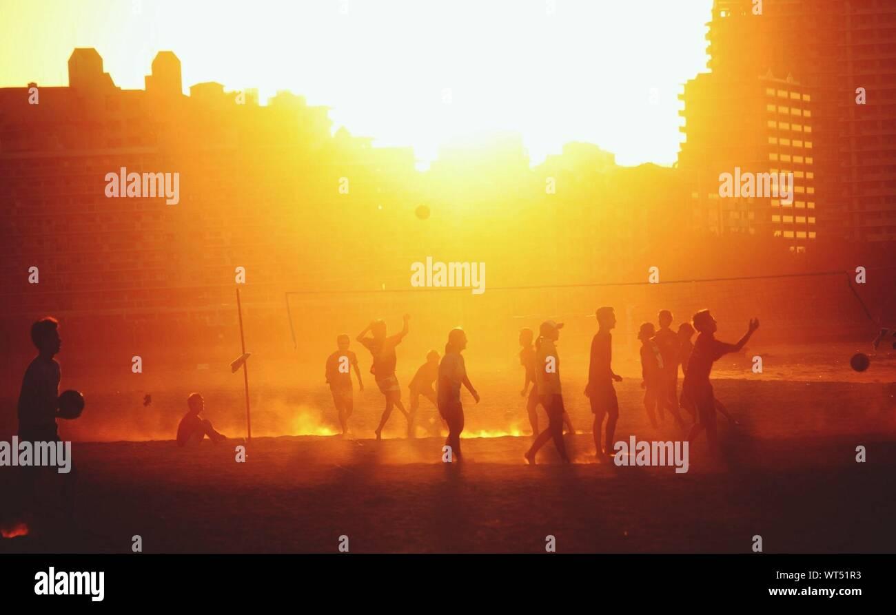 Les gens à jouer au volleyball de plage au coucher du soleil Banque D'Images
