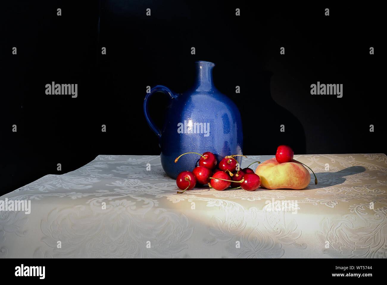 Fruits et Vase bleu sur le tableau sur fond noir Banque D'Images