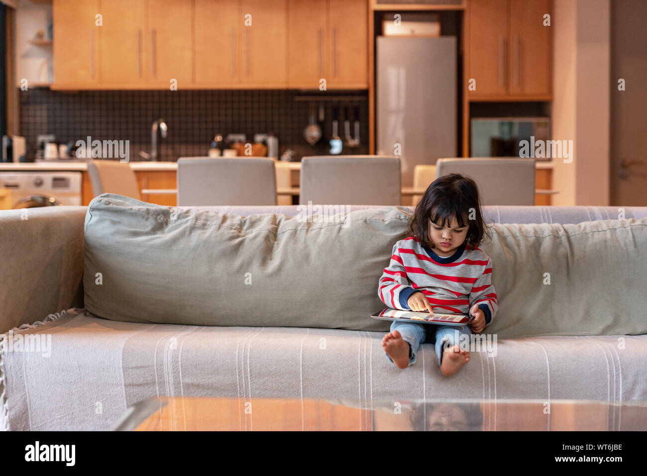 Jolie petite fille assise sur son canapé à l'aide d'une tablette Banque D'Images