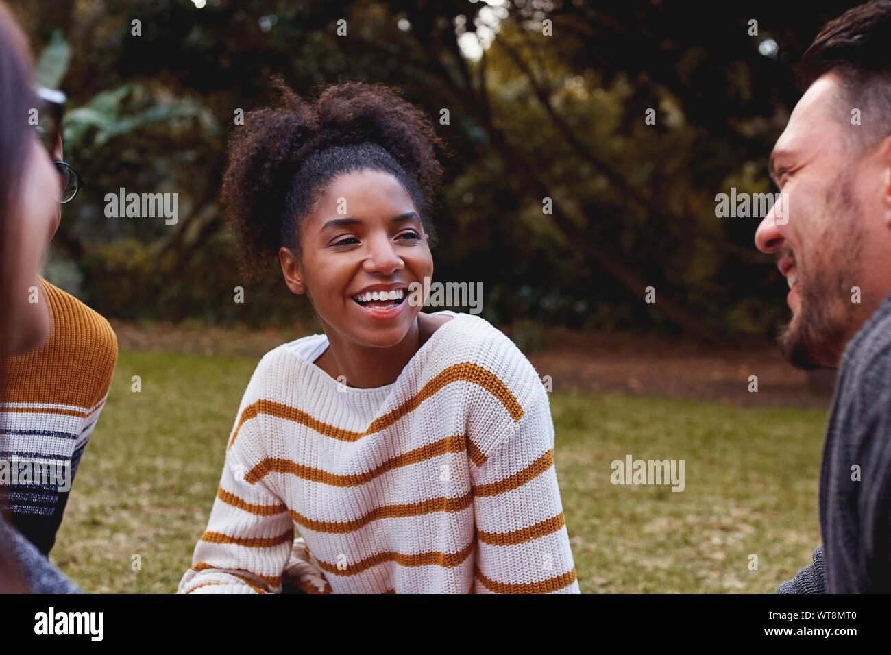 Portrait of a smiling african woman et profiter avec ses amis dans le parc Banque D'Images
