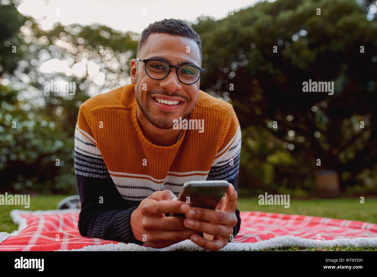 Portrait of a smiling african american man lying on blanket in the park holding mobile phone dans la main à la caméra en souriant Banque D'Images