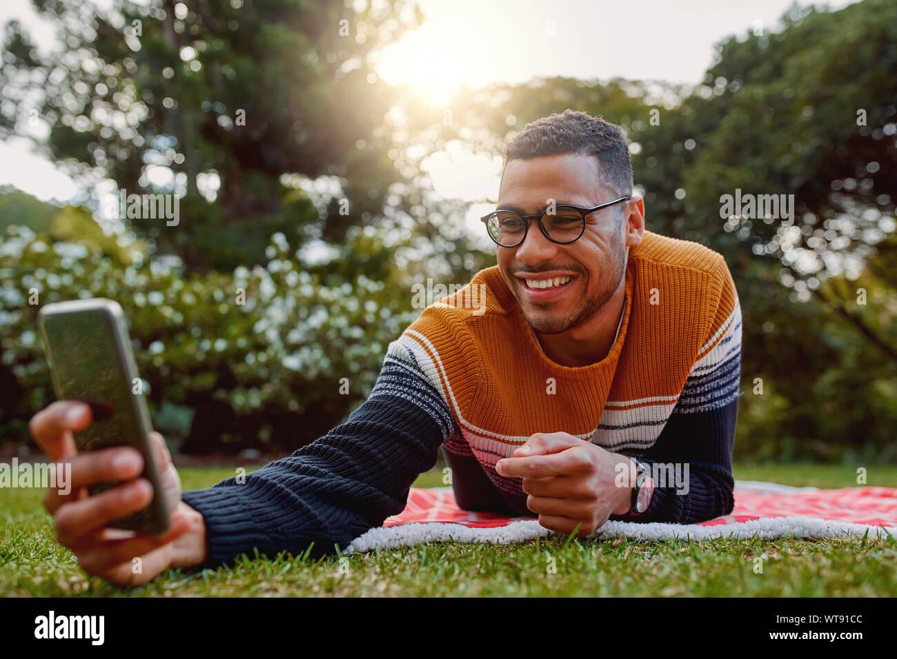 Portrait of a smiling young african american man lying on blanket sur l'herbe verte dans le parc en tenant sur selfies téléphone mobile au collégial - universitaire Banque D'Images